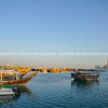 Traditional style dhow boats moored in Dhow Harbor ready for tourist cruises.