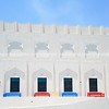 Red and blue bench seats outide white building with Arabic or Islamic design details.