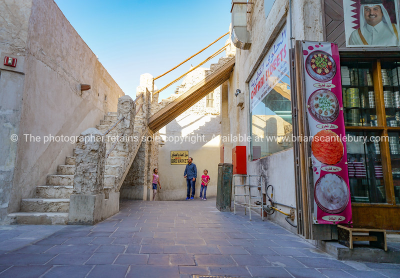 Father and two children wait at end of shady lane in Souq Waqif traditional markets.