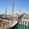 Moored dhow with rope rigging on Doha waterfront with House of Parliament background.