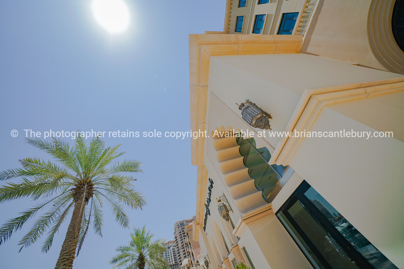 Architecture with Islamic detail and palm trees against blue sky with sun burst