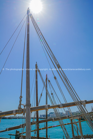 Ropes and spars of traditional rigging of dhow moored along Doha Old Town waterfront.