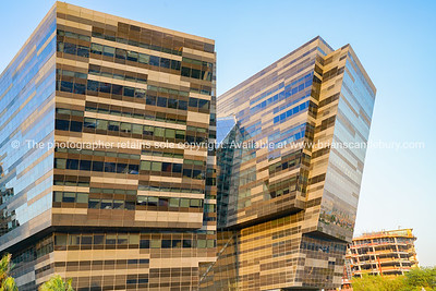 Al Hitmi, modern office building with striking glass facade with one tower looking like its falling.