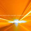 Bright lights in motion blur whist moving towards end of a tunnel,