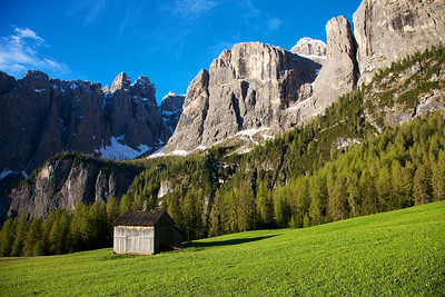 Dolomite Mountain Hut in a green meadow during the early summer.  Snow still covered the high peaks above.