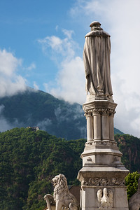 Bolzano Statue of Walther a hero of the city.  The town square is named after this man and his statue towers high in its center.  The distant mountains and clouds made a lovely morning scene.