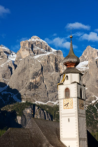 Corvara Church Tower with snow-covered mountains in the distance.