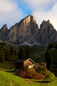 Mountain Hut Morning the first light of the day touched the jagged peak and then illuminated the small hut.  The golden light slowly warmed up the Dolomites.