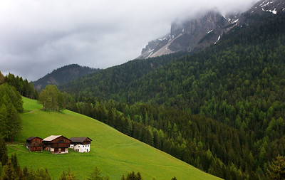 Three Dolomite Cabins face the rugged cliffs of the Puez Odle mountains, Italy