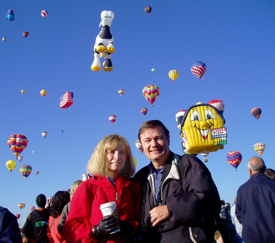 """We paused briefly and turned our attention from the skies to have our """"we were there"""" picture made in the midst of the nearly 20,000 spectators.  Unlike many other balloon festivals, there are no viewing stands at the Albuquerque event; guests walk the field amidst the hundreds of hot air behemoths."""