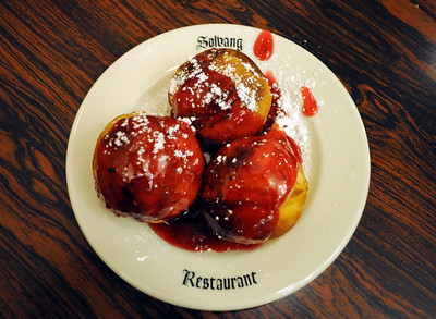 """For dessert we had the house speciality - """"aebleskivers,"""" best described as round pancake balls served with raspberry jam and powdered sugar."""
