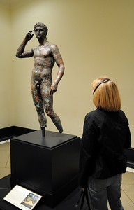 This Greek statue of a victorious young athlete crowning himself with a wreath was found in the sea; it was probably once the cargo of a Roman ship that foundered during the first century B.C. or A.D.  while sailing from Greece.  It is one of vert few life-size Greek bronzes existing today.
