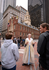 Wearing the period dress of the 18th century, a local tour guide describes the history of Boston's Old State House to a group of visitors.