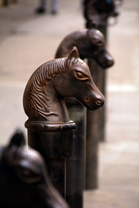 """In the French Quarter, you will occasionally see some cast iron posts on the sidewalk with a horse's head mounted on top.  Although most today are simply decorative, they historically had a purpose. In the """"mouths"""" of the original cast iron horse heads, there would be a large ring where someone could tie off their horse while inside a building."""