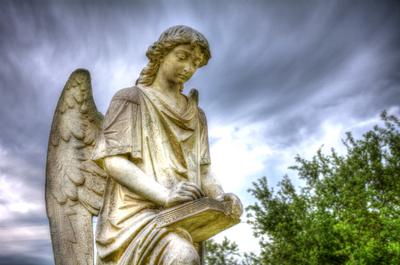 """It's called """"The Turning Angel,"""" so-named because when cars drive by at night and their headlights shine on the monument, it appears to turn. It overlooks the grave sites of five employees of the Natchez Drug Company – all young women and girls – who were killed in a massive explosion in 1908. The explosion put the company out of business, but the owner was so devastated that he purchased a lot to bury his employees along with this angel monument. His youngest employee was 12 years old."""