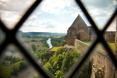 Beynac Window overlooking the Dordogne River and the Beynac church.  The view through the old glass warps the view in an original way.