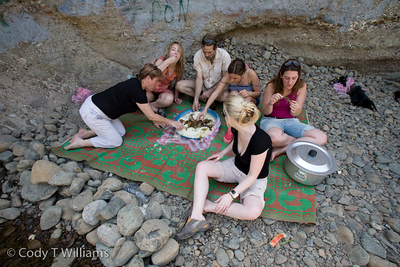 Foreigners share a picnic lunch of locals while waiting for their vehicle to be fixed in a river canyon of the Hajar Mountains near Hatta, United Arab Emirates (UAE), May 25, 2009. /© Cody Williams.