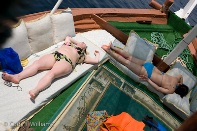 Tourists sun bath on the deck of a boat out to sea on the coast of Oman, May 26, 2009. /© Cody Williams.