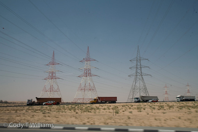 A train of cargo trucks pass in front of tall power towers along a stretch of highway in Dubai, United Arab Emirates (UAE), May 25, 2009. /© Cody Williams.