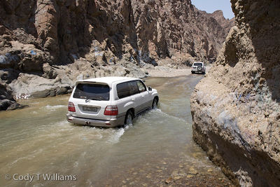 4x4 SUVs drive through a river canyon of the Hajar Mountains near Hatta outside Dubai, United Arab Emirates (UAE), May 25, 2009. /© Cody Williams.