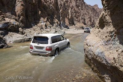 4x4 SUVs drive through a river canyon of the Hajar Mountains near Hatta outside Dubai, United Arab Emirates (UAE), May 25, 2009. /© Cody Williams.
