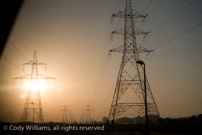 The sun sets beyond power lines across a developing Dubai, United Arab Emirates (UAE), May 26, 2009. /© Cody Williams.