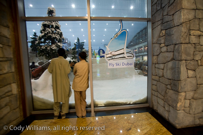 Two mall walkers peer into a window to see the slope of Dubai Ski, a full service indoor ski resort in the Mall of the Emirates, Dubai, United Arab Emirates (UAE), May 28, 2009. /© Cody Williams.