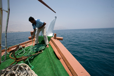 A man pulls up the anchor of a boat out at sea on the coast of Oman, May 26, 2009. /© Cody Williams.