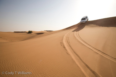 A 4x4 SUV crests a sand dune during a desert safari in a desert region of Dubai, United Arab Emirates (UAE), May 25, 2009. /© Cody Williams.
