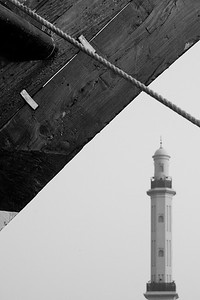 The minaret of the Grand Mosque, framed by a moored dhow boat.