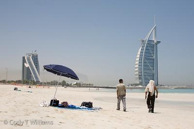 Two men walk toward the luxury hotel Burj Al Arab along the Jumeirah Beach, Dubai, United Arab Emirates (UAE), May 28, 2009. /© Cody Williams.