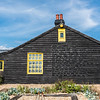 Another black house, wooden with yellow window. What is interesting is the writing on the house. Very interesting, I have never seen a house with writing like this on its wall.