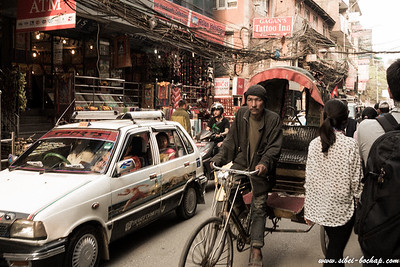 Cars and trishaws and pedestrains pack shoulder to shoulder in Thamel's narrow and dusty streets