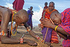 Masai warriors starting a fire with sticks and elephant dung.