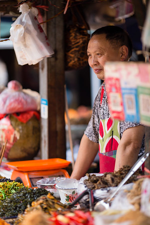 Vendor at a street vegetable market  in Chengdu, China.