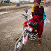 A local man sitting on his motorbike on the outskirts of Yarchengar Tibetan Buddhist Monastery in Sichuan, China.