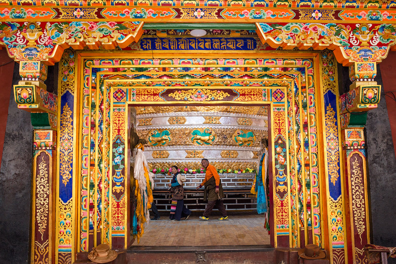 Local Tibetan Buddhist pilgrims do the small kora around a prayer wheel in the town of Lithang in Sichuan, China.