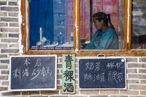 A young girl prepares food in a local restaurant in the town of Langmusi in Sichuan, China.