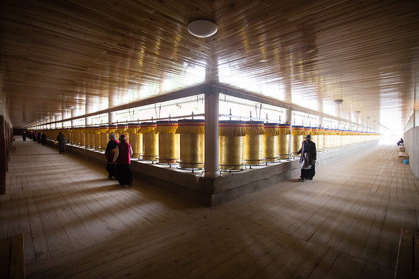 Local pilgrims perform the kora pilgrimage around a set of prayer wheels in the town of Lithang in Sichuan, China.
