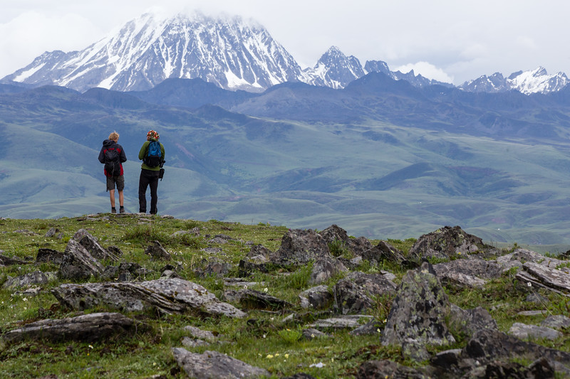 Hikers overlooking the mountains near Tagong in Sichuan, China.