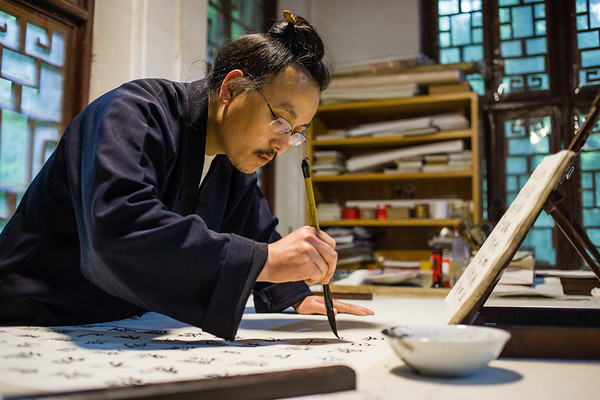 A Taoist monk practices calligraphy in a temple on Qingcheng mountain near the city of Chengdu in Sichuan, China.