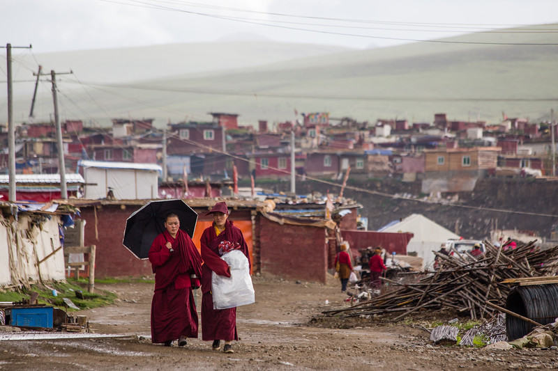 Two nuns walking through the streets of Yarchengar Tibetan Buddhist Nunnery in Sichuan, China.