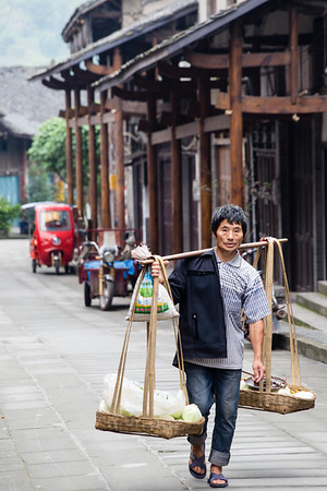 A local man carries good through the streets of small-town Lizhuang in Sichuan, China.