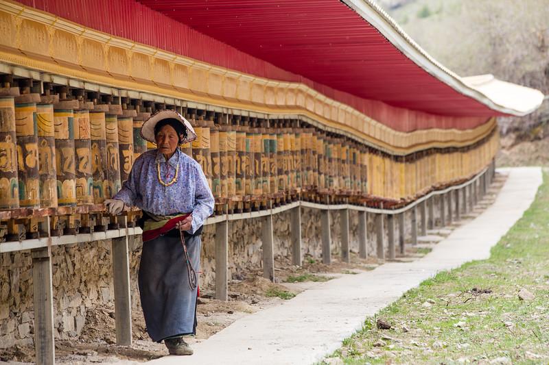 A Tibetan Buddhist pilgrim makes a kora of prayer wheels outside the town of Songpan in Sichuan, China.