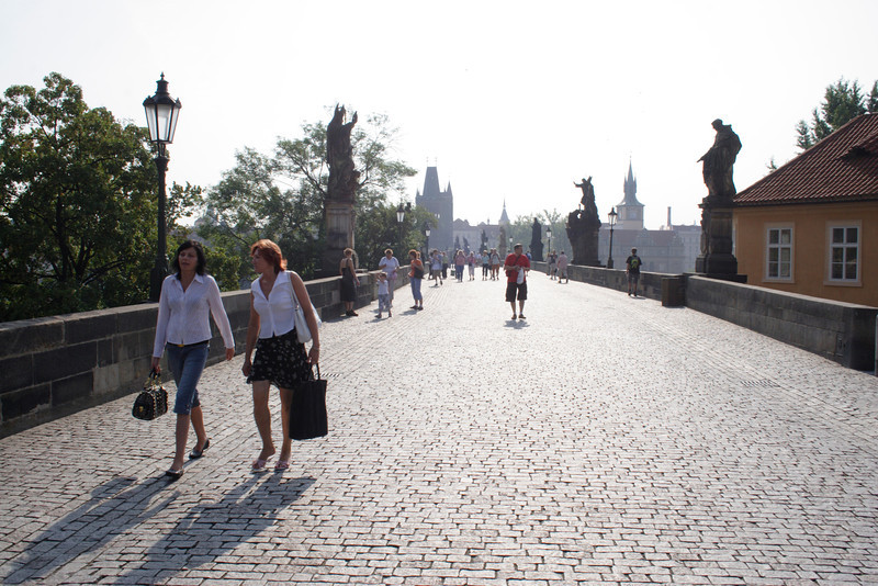 Young women walking across Charles Bridge Prague in early morning August 2007