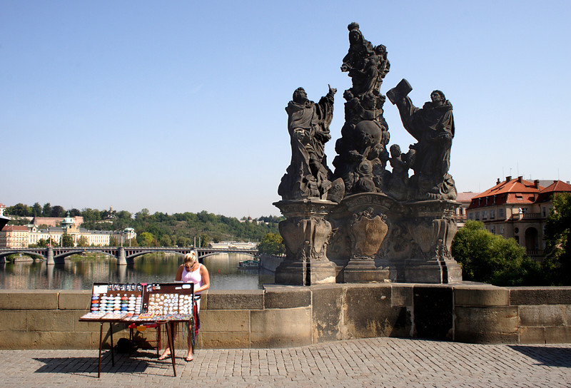 Souvenir stall and statue of The Madonna St Dominic and St Thomas on Charles Bridge Prague