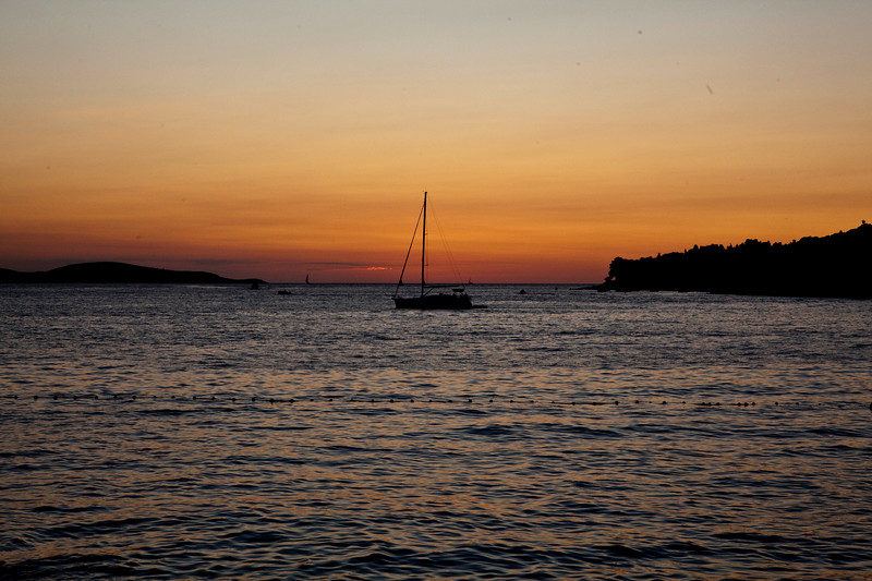 Sunset over the water at the port of Hvar, Croatia with a sail boat crossing the small channel under power.