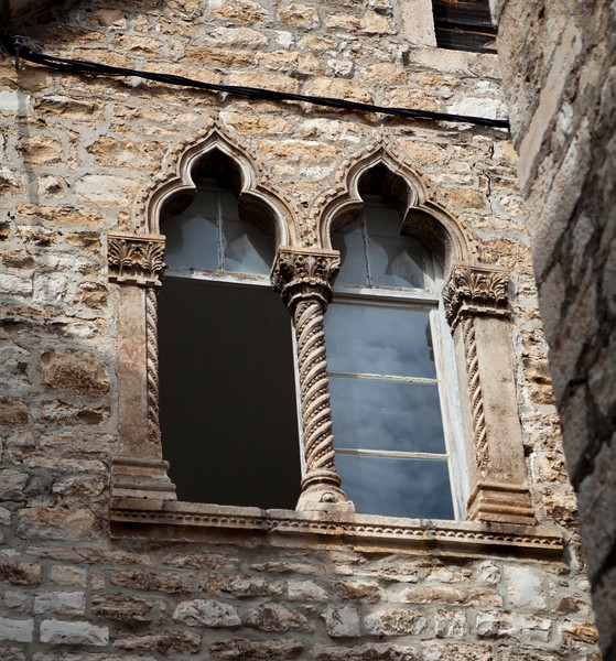A pair of very decorative windows are typical of the beauty found in the old buildings on Hvar, Croatia. This was taken on a small street of a building of no particular consequence or significance.