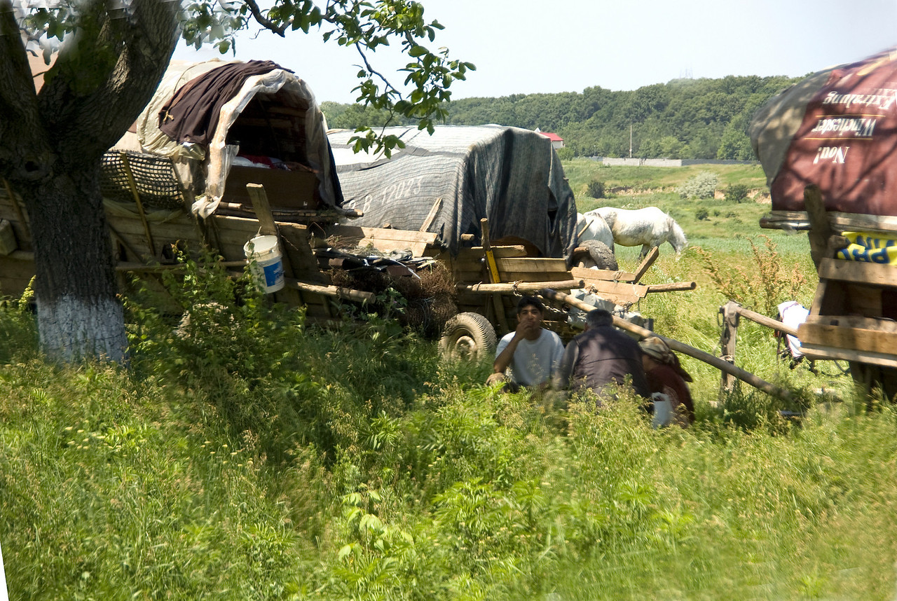 Romanian gypsy caravan with gypsies siting in shade of the tree