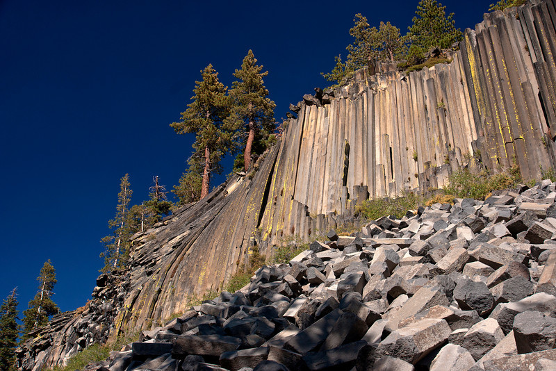Late afternoon view of the Devil's postpile.<br /> A lot of the broken columns lie in a pile at the bottom and you can see the hexagonal structure a lot more clearly in these broken pieces.